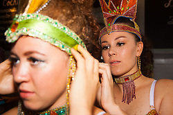 London, August 25th 2014. Final touch ups to costumes are made as Notting Hill Carnival goers prepare to party despite the pouring rain.