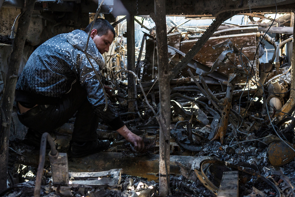 MARIUPOL, UKRAINE - MAY 10: A man searches inside a burned tank a day after deadly clashes on May 10, 2014 in Mariupol, Ukraine. A referendum on greater autonomy is planned for the region tomorrow. (Photo by Brendan Hoffman/Getty Images) *** Local Caption ***
