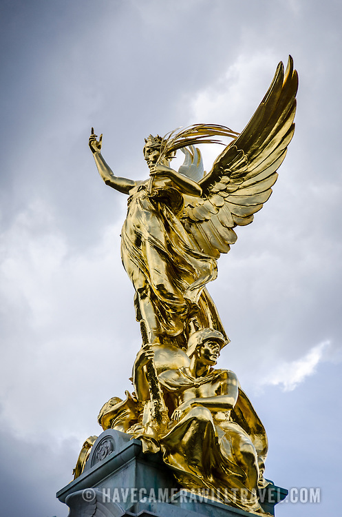 Gold Statue on Victoria Memorial Buckingham Palace London against Cloudy Sky 169-111114777 The Victoria Memorial, dedicated to Queen Victoria, sits directly in front of Buckingham Palace, with Queen Victoria facing The Mall.