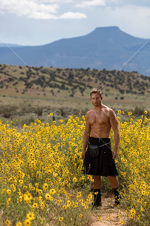 sexy man without a shirt in a kilt outdoors