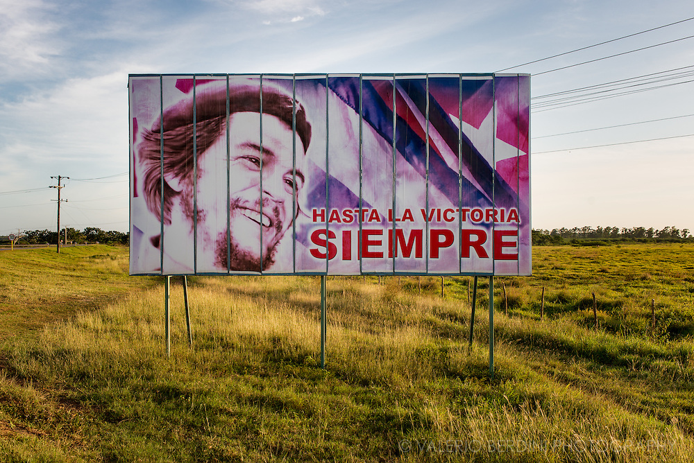 """A poster of Che Guevara with his famous quote """"Hasta la victoria siempre"""" (""""Until victory, always!"""") lit by the warm afternoon light in a road approaching Cienfuegos, in the centre of Cuba"""