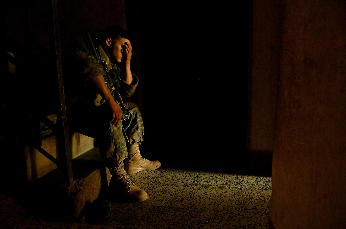 SPC Jason Dickerson from Bravo Company, 2-6 Infantry, Task Force 1-35 Armored Division, Baumholder, Germany, sits on some steps of a home and wipes sweat from his face while his team questions an Iraqi family and fills out a census in their home in Tameem, Ramadi, Iraq on August 7, 2006. The census is geared to finding out general information on the Iraqi household and to see if they have any concerns or questions they can help with. — © TSgt Jeremy Lock/