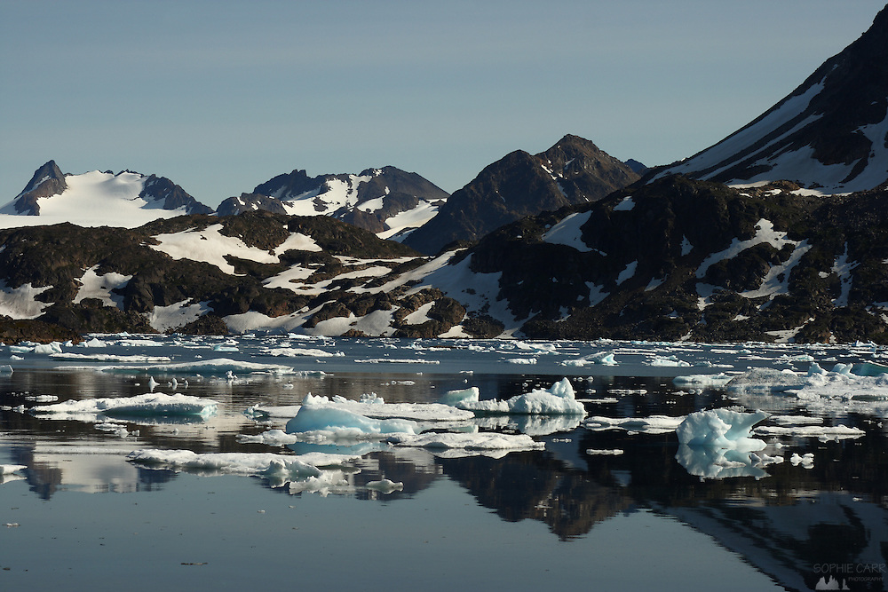 Mountains and icebergs relfected in a fjord in Kulusuk, south-east Greenland