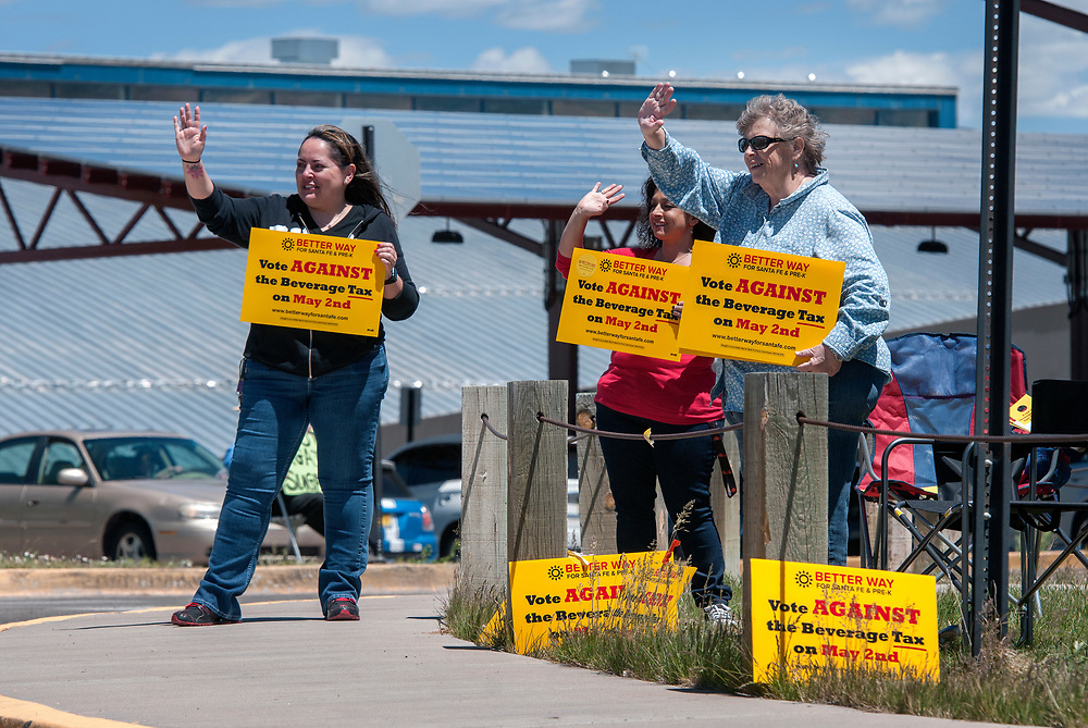 em050217e/a/From left, Sarah Vigil, Pamela Miera and Jeanne Sellers hold signs opposing a tax on sugary drinks to fund Pre-K for kids in Santa Fe. This was in front of the Genoviva Chavez Community Center in Santa Fe, Tuesday May 2, 2017. (Eddie Moore/Albuquerque Journal