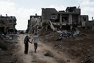 Gaza Strip, Khuza'a: A couple of Palestinians walk by destroyed houses on a street in Khuza'a village on August 3, 2014. ALESSIO ROMENZI