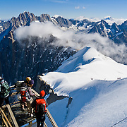 See the Needles of Chamonix (Aiguilles du Chamonix) and Mont Blanc massif from spectacular Aiguille du Midi station (12,600 feet) on the téléphérique (cable car, aerial tramway, or Seilbahn) from Chamonix (3300 feet elevation), France, the Alps, Europe. Published in Wilderness Travel 2015 Catalog of Adventures.