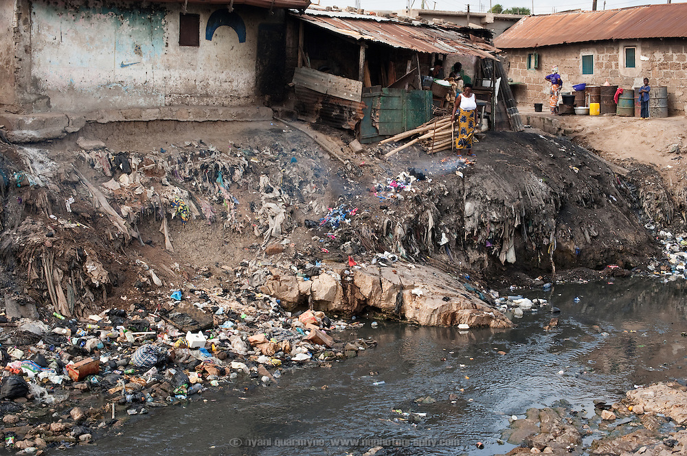 A severely polluted river divides east and west Nima, a densely populated area of Ghana's capital, Accra. Both sides of the community slope down to the river,  washing trash and debris into the watercourse when it rains. In addition, in the absence of adequate waste collection and sanitation, the river serves as a de facto dumping ground and a latrine. Sanitation workers regularly clear the waterway, but refuse is not collected, only raked to the banks to allow the water to flow. As adequate waste disposal facilities do not exist, a woman is seen buring her garbage on the banks.