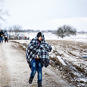 After crossing the Macedonian-Serbian border, a young refugee walks the unofficial refugee route in subfreezing snowy weather. Near Miratovac, Serbia, January 17, 2016. <br /> <br /> According to UNHCR, 67,415 refugees landed in Greece in January 2016 alone, most of who traveled the route through Serbia on their way to Western Europe. The number of refugees arriving in Greece has dropped significantly since the Balkan border closures in March 2016.<br /> <br /> On assignment for Mercy Corps, I documented refugees crossing through Serbia in January 2016.