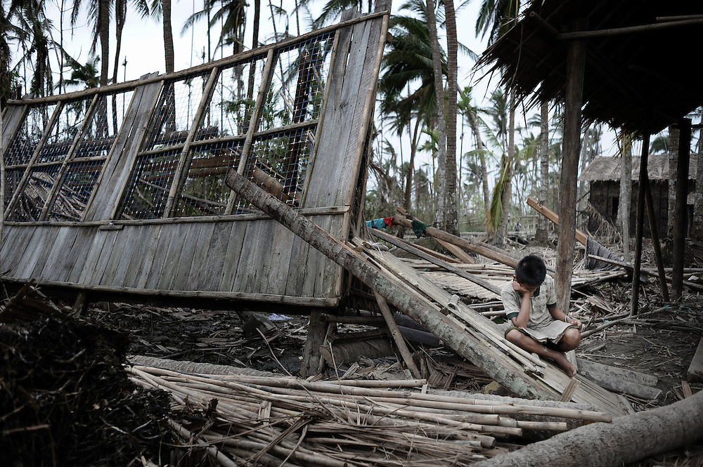 A young boy from Kayadaung reads a book while sitting on the wreckage of his house on May 23, 2008 in the isolated area of Kanzeik in the Irrawaddy Delta region -- an area only accessible by boat which has received neither government nor foreign aid. Voters in regions devastated by the cyclone, many hungry and destitute, cast ballots on May 24 in a referendum that many said was meaningless because Myanmar's junta has already declared victory.