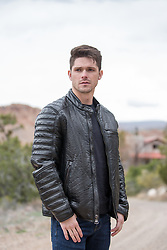 hot man in a black leather jacket outdoors