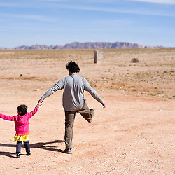 032713       Brian Leddy<br /> Amya Smith, left, walks with Keyvan Izadi Tuesday near Bodaway Gap, Ariz. Izadi was at the family's home to help with the installation of solar lights at their residence, which has no electricity.