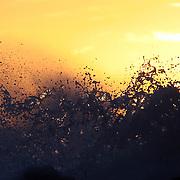 CHILE - Region VIII Bio Bio - Cobquecura.A wave breaks onto rocks at sunset on Pilicura Beach   2007
