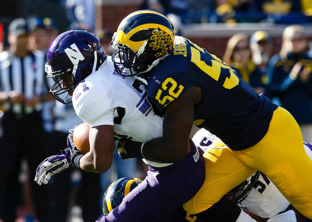 Oct 10, 2015; Ann Arbor, MI, USA; Northwestern Wildcats running back Justin Jackson (21) is tackled by Michigan Wolverines linebacker Royce Jenkins-Stone (52) in the first quarter at Michigan Stadium. Mandatory Credit: Rick Osentoski-USA TODAY Sports