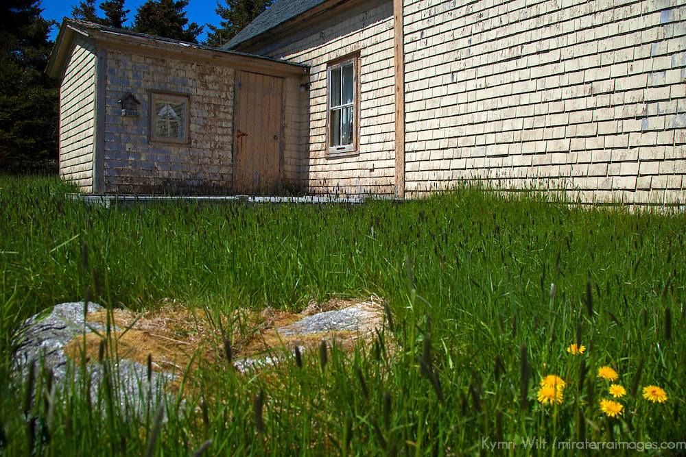 North America, Canda, Nova Scotia, Guysborough County. Grassy yard of yellow weathered home of Nova Scotia.
