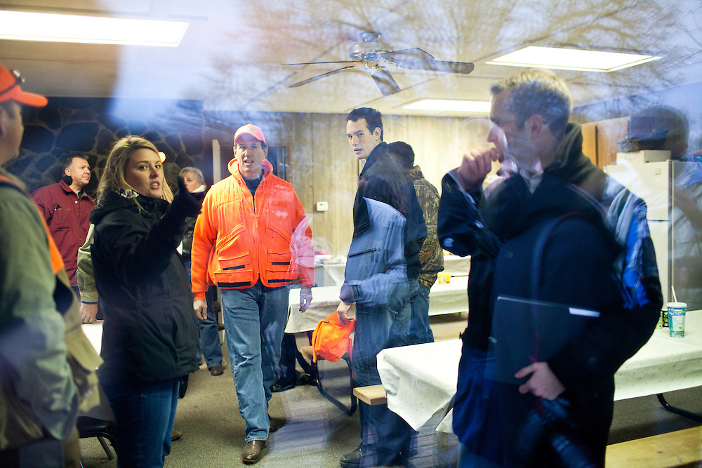Republican presidential candidate Rick Santorum, in orange coat, confers with staff before a news conference on Monday, December 26, 2011 in Adel, IA.