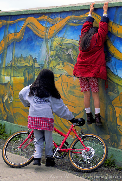 Americas, South America, Chile, Puerto Natales. Two young girls can't resist a peak over the wall of the local futbol stadium in Puerto Natales. Caught in mid-hang, did she fall before the other girl got the bike seat under her feet? No! She didn't!