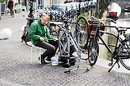 In Utrecht plakt een man de achterband van zijn fiets.<br /> <br /> In Utrecht a man is fixing the flat tire of his bicycle.