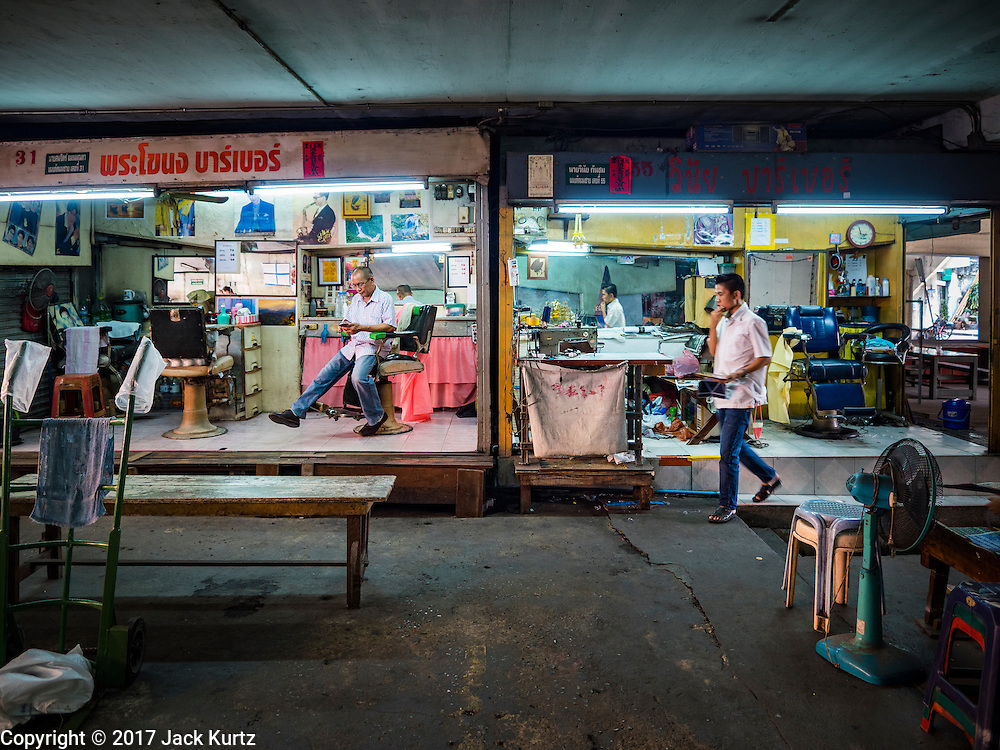 "06 FEBRUARY 2017 - BANGKOK, THAILAND: A man walks past some of the barbershops in what used to be known as Kalabok Market under the Phra Khanong Bridge in the Phra Khanong district of Bangkok. Kalabok is the Thai word for hairdresser and the market was called Kalabok because there were many barbershops and hairdressers under the bridge. In 1985, the city changed the name of the market to ""Singha Market."" There are still about 10 small men's barbershops, most with just one barber, and four women's salons, most with one hairdresser,  under the bridge.      PHOTO BY JACK KURTZ"