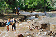 BOULDER, CO - SEPTEMBER 13: Cassidy Crittenden (left), 13, and Molly Gallagher, 15, walk through flood waters in the middle of Topaz Street in Boulder, Colorado as heavy rains for the better part of week fueled widespread flooding numerous Colorado towns on September 13, 2013. Local residents said the Four Mile Canyon Creek that runs nearby is usually a trickle at this time of year. (Photo by Marc Piscotty/ © 2013)