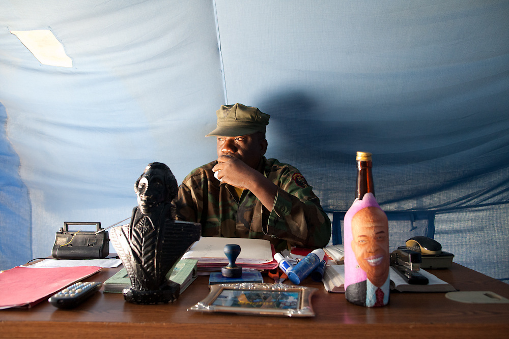 """Sergeant Chery Samson, talks on a phone at his desk in a small tent in a densely populated neighborhood in Petion-Ville. On Samson's desk is a bust of Toussaint L'Ouverture (who led the Haitian slave revolt and defeated Napoleon) and a rum bottle with a President Michel Martelly's face painted on it. Samson says that he is in charge of all of the troops in Haiti. Samson keeps a copy of the Haitian constitution on his desk and qoutes article 267-3 which says """"(the government) does not have the right to decommission the military... the government does not have the right to put the military on leave"""" Samson who was in the Haitian army from 1980 to 1995 says """"even though we didn't have resources we've always been the military and have always defended the interests of the military and the country"""" and """"January 12th, the earthquake happened I was saving an old person's life and a house collapsed on me and I lost my hand. When I was in the hospital several commanders came and visited me and we decided that we needed to start getting organized and set up offices to control the whole army and we started re-mobilizing. .We are waiting for Michel Martelly to name the minister of defense and the major for the army. We are all in little groups and at that time we'll come together."""""""