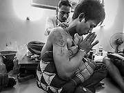 """07 MARCH 2015 - NAKHON CHAI SI, NAKHON PATHOM, THAILAND: A man prays after getting a new tattoo at the Wat Bang Phra tattoo festival. Wat Bang Phra is the best known """"Sak Yant"""" tattoo temple in Thailand. It's located in Nakhon Pathom province, about 40 miles from Bangkok. The tattoos are given with hollow stainless steel needles and are thought to possess magical powers of protection. The tattoos, which are given by Buddhist monks, are popular with soldiers, policeman and gangsters, people who generally live in harm's way. The tattoo must be activated to remain powerful and the annual Wai Khru Ceremony (tattoo festival) at the temple draws thousands of devotees who come to the temple to activate or renew the tattoos. People go into trance like states and then assume the personality of their tattoo, so people with tiger tattoos assume the personality of a tiger, people with monkey tattoos take on the personality of a monkey and so on. In recent years the tattoo festival has become popular with tourists who make the trip to Nakorn Pathom province to see a side of """"exotic"""" Thailand.   PHOTO BY JACK KURTZ"""