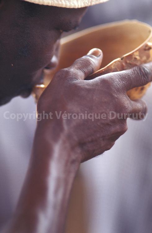 Homme buvant du dolo, une sorte de bière à base de mil fermenté, dans une calebasse, pendant une cérémonie funéraire, dans la région de Bobo Dioulasso.
