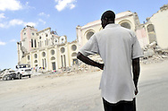 A man pauses near the collapsed Roman Catholic Cathedral in Port-au-Prince, Haiti on Saturday, January 30, 2010. Archbishop Serge Miot was killed when the 18th. century cathedral was destroyed in the massive 7.0 earthquake on January 12th., killing upwards of 300,000 people.