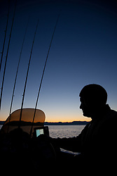 """Sunrise Fishing on Lake Tahoe 1"" - This silhouette of a man was photographed on his fishing boat at sunrise on Lake Tahoe."
