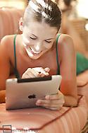 Junge, hübsche Frau im Sommer, Urlaub, in der Lobby, surft mit iPad im Internet (Modellfreigabe)