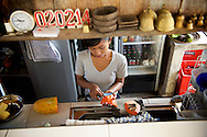 A waitress prepares fresh papaya at a cafe in Ubud, Bali, Indonesia.