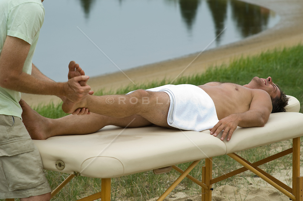 Man enjoying a massage outside beside calm water