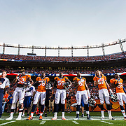 Denver Broncos players stand for the National Anthem before an NFL preseason game against the San Francisco 49ers on Saturday, Aug. 29, 2015 in Denver. The Broncos won the game, 19-12. (Ric Tapia via AP)