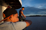 Brazilians and Colombians peer out at river backs of the Amazon during sunset aboard Avenger III. The Avenger III is a passenger ship making the twice a month journey from the frontier town of Tabatinga in the Tr&ecirc;s Fronteiras region of Northwestern Brazil, to the capital of the State of Amazonas, Manaus. It&rsquo;s also where the Rio Amazonas enters Brazil from its source in neighboring Peru. <br /> <br /> Carrying passengers and crew totaling almost 200 and small cargo, the ship meanders its way along the Rio Amazonas and Rio Solimoes for four days and three nights. Stopping at half a dozen or so makeshift ports en-route, the service provides a vial link for communities along the river to get products to the city and more importantly, in the absence of roads or airfields, provide a means for the sick to reach care in the city of Manaus.<br /> <br /> For those not fortunate to be accommodated in one of the two or three cabins available, home is space found for a self supplied hammock amongst the kaleidoscopic web of coloured fabrics. <br /> <br /> By the second day, negotiating a stroll from port to starboard can seem more like negotiating an assault course of tangled ropes and personal baggage deliberately piled high to protect ones personal space.<br /> <br /> Food served three times daily is adequate, a staple of soups, chicken, rice and noodles. An &lsquo;entertainment&rsquo; deck on the top floor provides ample opportunity to be social engaging in card and board games with beer swilling, chain smoking locals.