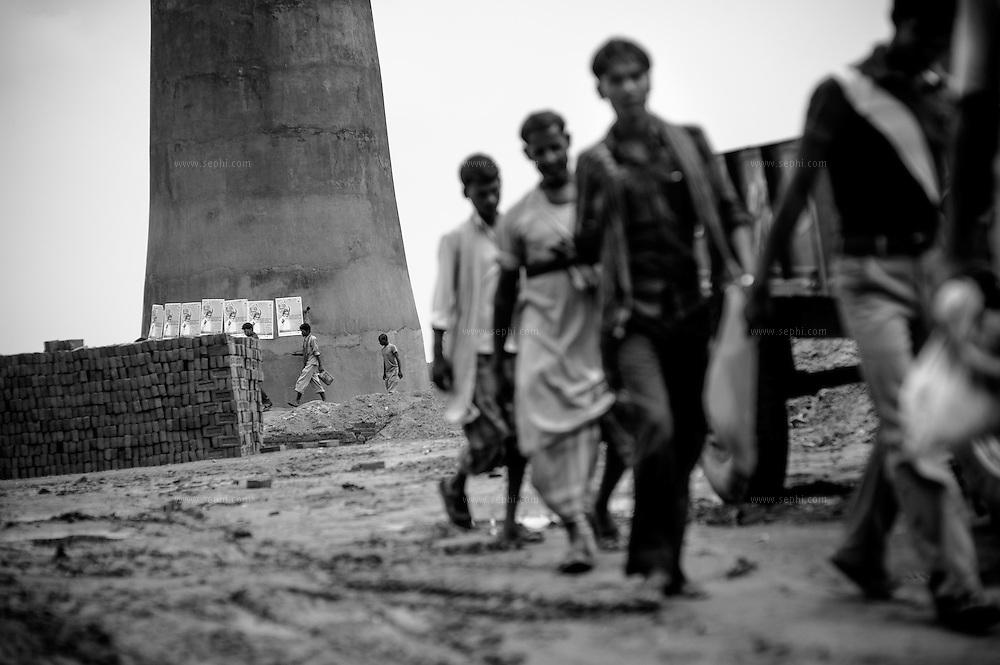 Workers pass by IEC material put up on one of the chimneys of the brick kilns on the outskirts of Patna, Bihar