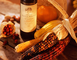 A bottle of wine sits at the ready for a fall feast among squash, pumpkin, corn stalks, nuts, and a basket of cranberries.