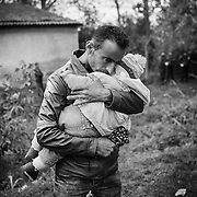 A father cuddles his child while waiting for a bus in a makeshift camp near Tovarnik's train station, Croatia.<br />