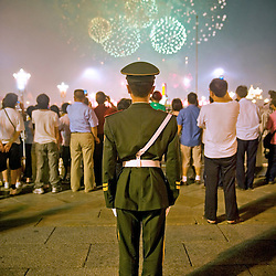 A Chinese military policeman watches fireworks illuminate the sky next to the entrance of the Forbidden City during the closing ceremony of the Beijing 2008 Olympic Games  August 24, 2008. (Photo By Ami Vitale)