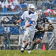 Duke midfielder Jake Tripucka #7  drives past defender. The third-ranked Fighting Irish defeated sixth-ranked Duke, 13-5, in men's lacrosse action on a snowy Saturday afternoon at Koskinen Stadium in Durham, N.C.