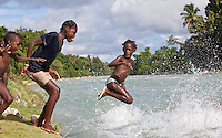 a girl jumps into a river near the Massif de la Hotte, Haiti