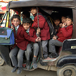 Kashmiri children load themselves up in a rickshaw on their way back from school in the city of Srinagar   in  Kashmir during Ramadan November 21.  Kashmir has seen nearly 1000 civilians killed this year alone and 1,765 wounded in a brutal conflict that the United Nations calls the most dangerous place in the world.  (Photo by Ami Vitale)