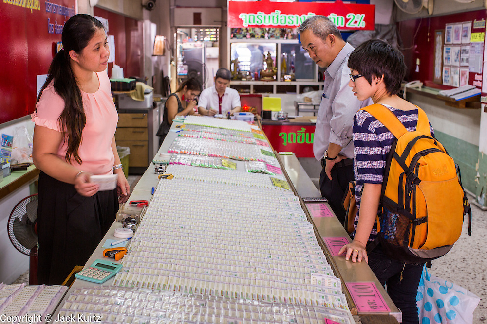 03 JANUARY 2013 - BANGKOK, THAILAND:  People buy lottery tickets at lottery shops along Sukhumvit Soi 77 in Bangkok. About 20 million Thais, nearly ? of the country's 65 million people, play lottery type games. The lotteries were brought to Thailand two hundred years ago by Chinese immigrants. Lottery agents are usually friends who collect bets but do not ask for money before the drawing.   PHOTO BY JACK KURTZ