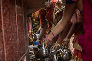 Women access clean water from a faucet at a Hindu Temple in Pondicherry, for a special meal prepared for the Ganesh Chaturthi Festival at the Chinna Mudaliyar Chavady.  Tamil Nadu, India. .