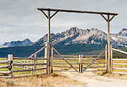 A ranch gate frames the Sawtooth Mountains near Stanley, Idaho, USA. The Sawtooth Range (part of the Rocky Mountains) are made of pink granite of the 50 million year old Sawtooth batholith.