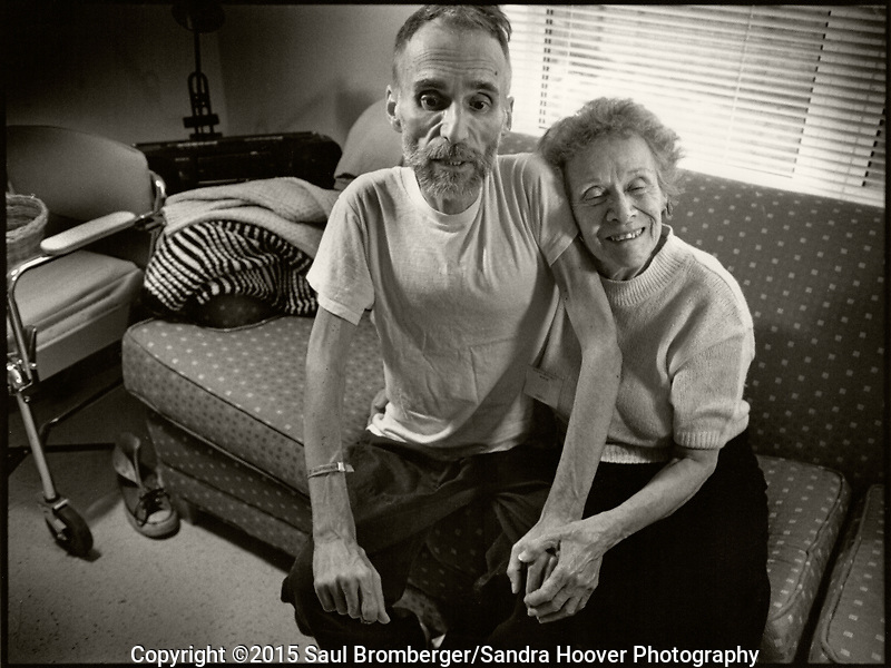 Documentary photo essay about some of the men and women living and battling the ravaging and horrific effects of AIDS, at the Bailey-Boushay House, an AIDS Hospice, in Seattle, WA., from June 1992 to April 1995.<br /> <br /> Opened in June 1992, B.B.H. was developed by AIDS Housing of Washington as the first new nursing care residence and day health program in America for HIV/AIDS patients.<br /> <br /> Our purposes were to humanize AIDS, to compel the viewer to say &quot;this could be me,&quot; and to educate those who did not see the disease and its victims face to face; and, to show the dignity and loving care that the B.B.H. community - the staff, volunteers, and families - provided to people living with AIDS in their final stages of life. &quot;It provides a respectful place for a major passage in life,&quot; said Administrator Christine Hurley.<br /> <br /> It gave us immense satisfaction that the portraits gave many of the clients a new sense of self esteem as they still felt worthy and important to be photographed, and that they trusted us to tell their story and share it.