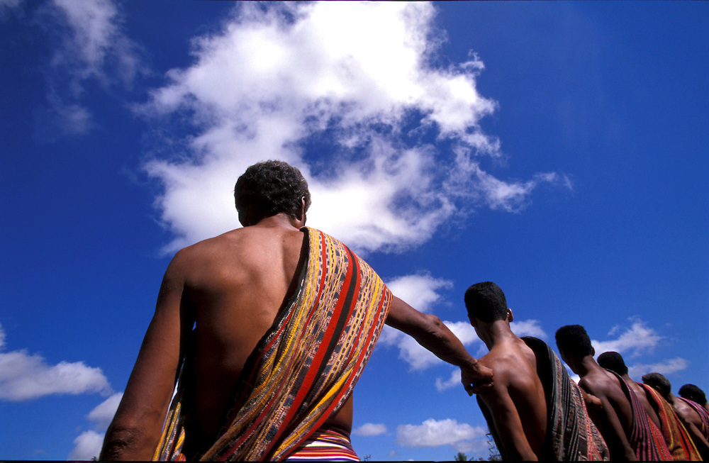 Group of men, seen from back,wearing the traditional Tais during the first anniversary of East Timor Independance in Lospalos. @ Martine Perret. 20 May 2003.