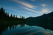 Wispy cirrus clouds are reflected in the waters of Mowich Lake, located along the Wonderland Trail in Mount Rainier National Park, Washington.
