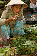 Vendor at Hoi An Central Market, Vietnam, taking a breakfast break to eat a bowl of Pho