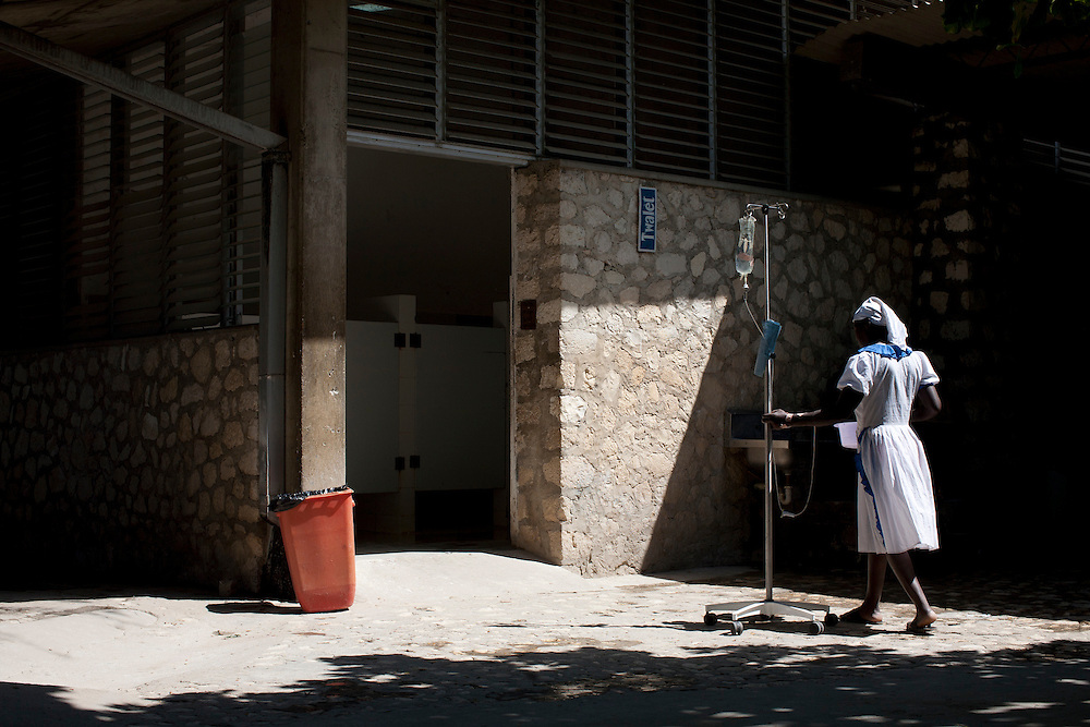A cholera patient makes her way, I.V. in tow, toward the toilet at the Hospital Albert Schweitzer on Thursday, October 28, 2010 in Deschapelles, Haiti.