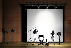 Movie set inside a sound stage with movie lights, movie camera, boom mic, director's chair, megaphone and clapper board