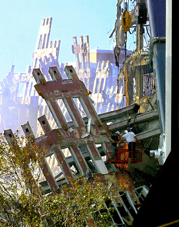 Steelworkers use torches to cut beams in the remains of the World Trade Center. This will allow rescue workers to search the lower reaches of the wreckage for possible survivors following the 9/11 attacks.